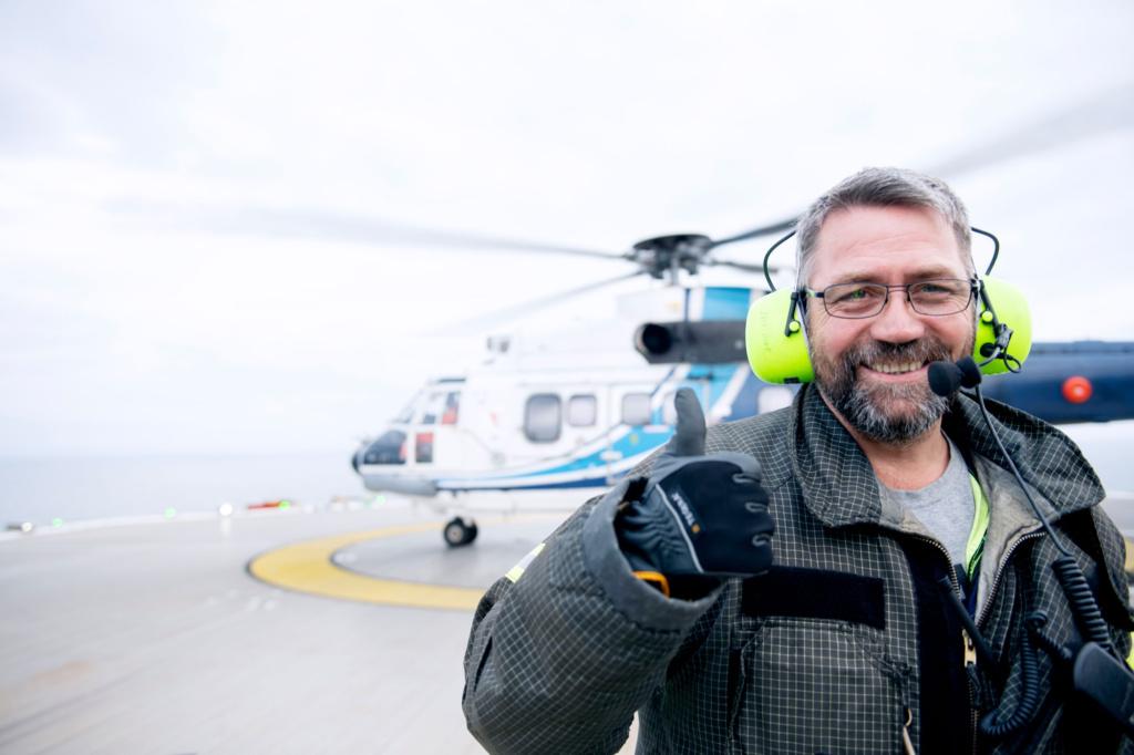 Mann står foran et helikopter. Foto