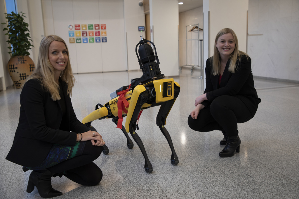 The Minister of Petroleum and Energy Tina Bru (right) handed down the PDO for the development of the Hod field to the robot dog Spot, accompanied by Lene Landøy, SVP Strategy and Business Development at Aker BP.